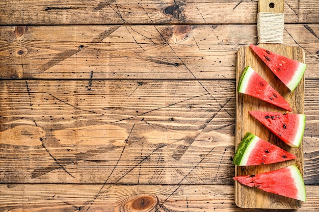 Heap of fresh red sliced watermelon. wooden background. top view. copy space.