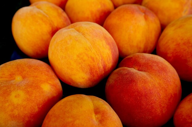 Heap of fresh ripe peaches for sale on the market