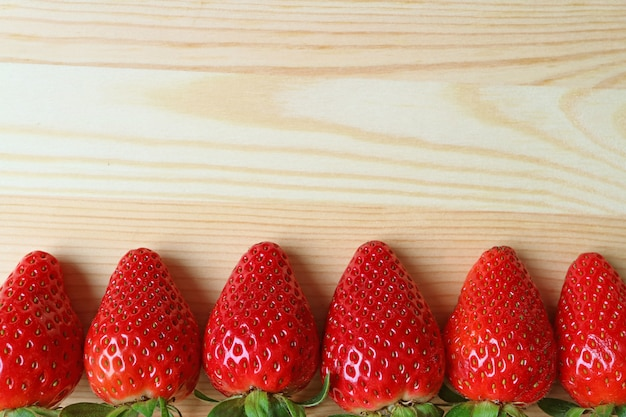 Heap of fresh ripe strawberry fruits lind up on wooden table with copy space