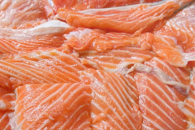 Heap of fresh sliced salmon fillet using as background