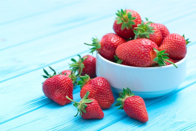 Heap of fresh strawberries in ceramic bowl on rustic white wooden table