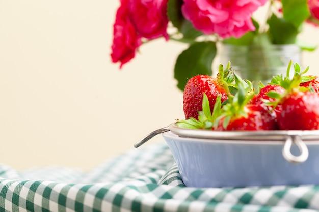 Heap of fresh strawberries in ceramic bowl on rustic