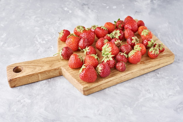Heap of fresh strawberries with cutting board. healthy nutrition