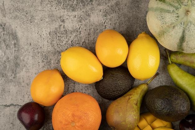 Mucchio di tutta la composizione di frutta fresca sulla superficie di marmo.