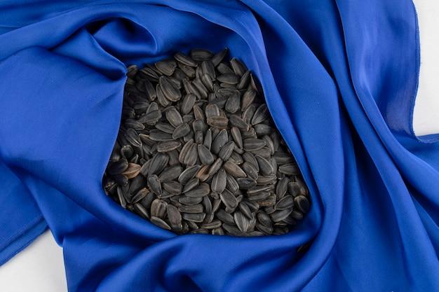 青いテーブルクロスの上に置かれたヒマワリの黒い種でいっぱいのヒープ
