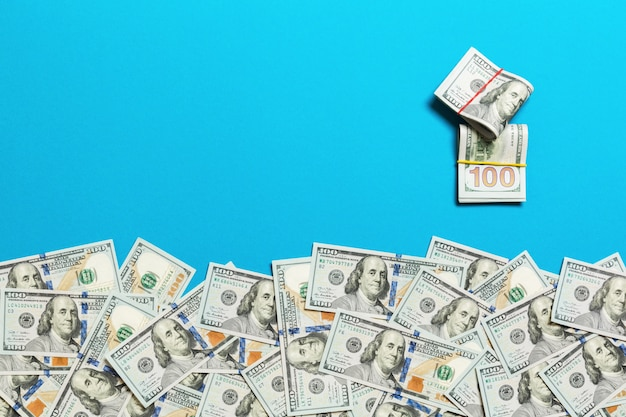 Heap of hundred dollar bills on coled background top view, with empty place  your text business money concept