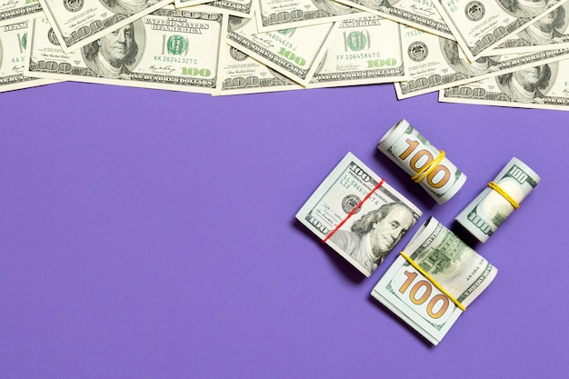 Heap of hundred dollar bills on colored surface top view, with empty place for your text business money concept