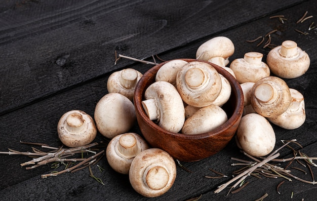 Heap of mushrooms, champignons in wooden bowl on black table, top view
