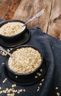 Heap of oats with milk in bowls