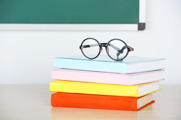 クラスのテーブルの上の本と眼鏡の山