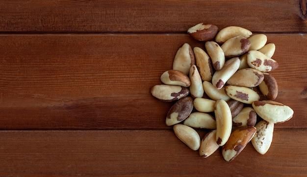 Куча бразильских орехов на старом деревянном фоне крупным планом вид сверху. бразильские орехи с дерева bertholletia excelsa