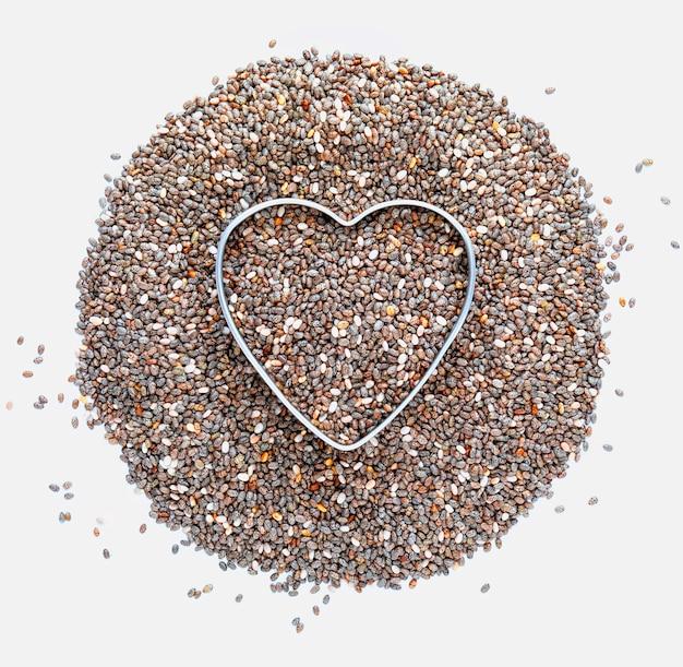 Куча семян чиа с сердцем любовь к чиа, изолированные на белой поверхности макро крупным планом с копией пространства