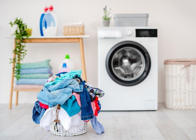 軽いバスルームの洗濯機の近くの床に立っているバスケットで洗うための服の山