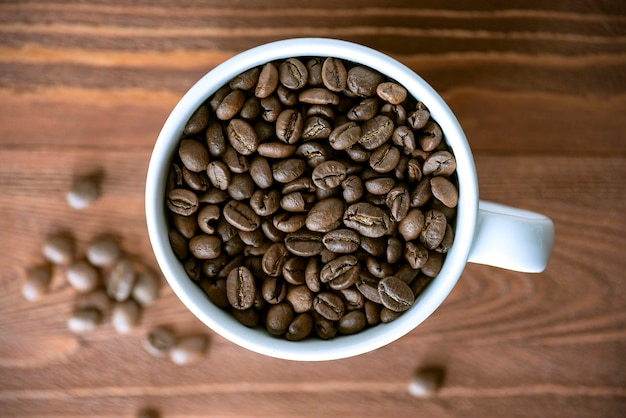 나무 테이블에 흰색 세라믹 머그잔에 커피 콩의 힙. 나무 표면에 볶은 커피 곡물, 평면도