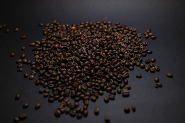 검은 배경에 커피 콩의 힙입니다. 검은 배경에 고립 된 커피 콩 더미입니다. 요리 커피 배경입니다.
