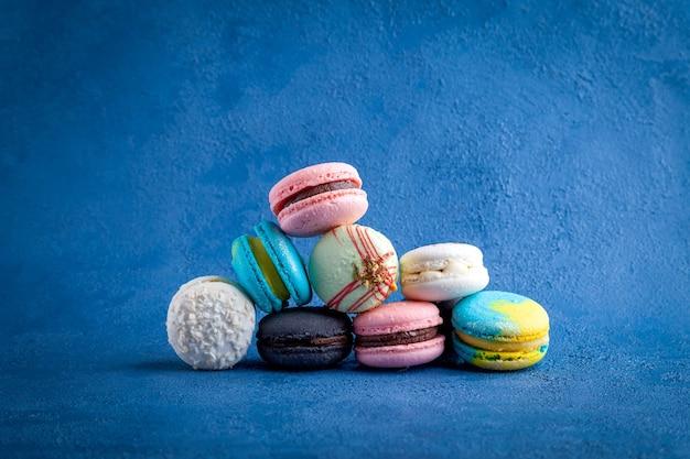 Куча цветного ассортимента макарон, сладкий традиционный французский десерт на синем фоне, крупный план горизонтального вида сверху, скопируйте место для текста