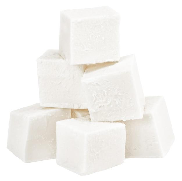 Куча нарезанного кубиками мягкого сыра, изолированные на белом фоне.
