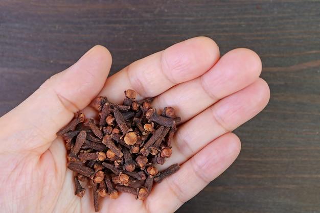 黒い木製の背景に手で乾燥したクローブのヒープ