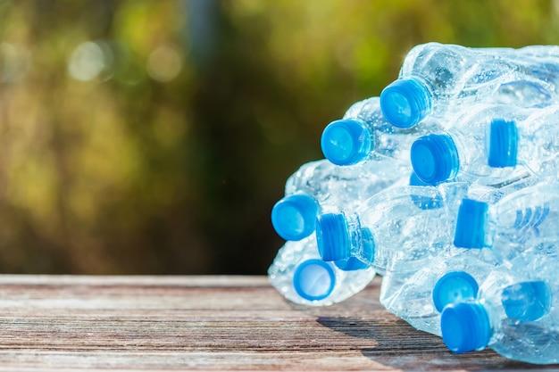 Куча пустой пластиковой бутылки с водой на деревянных досках