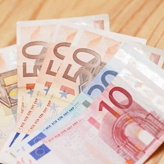Куча банкнот евро на деревянном столе