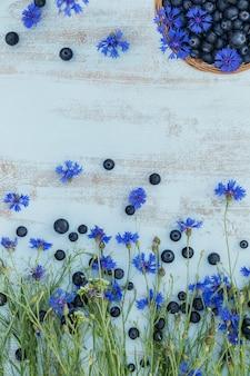 Куча свежей черники и цветов в корзине на белом деревянном