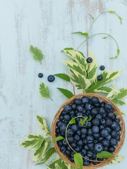 Куча свежей черники и листьев в корзине на белом деревянном. концепция здорового питания и диетического питания.