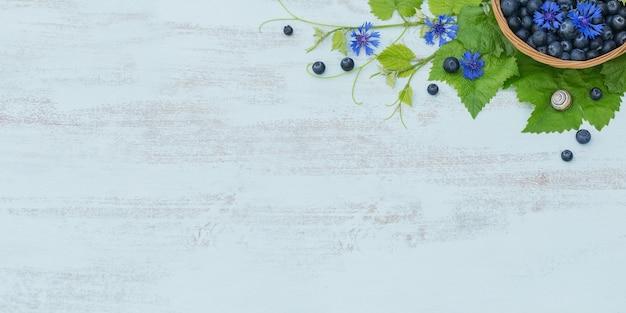 Куча свежей черники, цветов и листьев в корзине на голубом деревянном столе