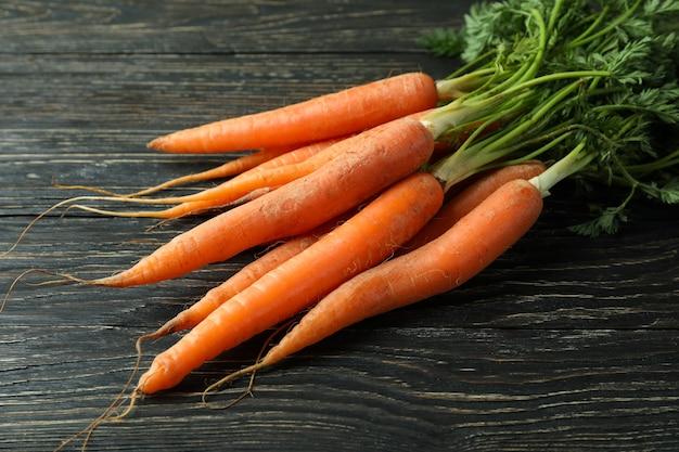 Куча свежей моркови на деревянных фоне
