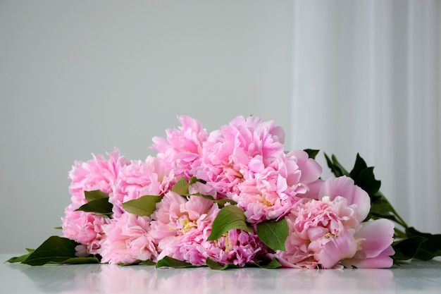 新鮮なヒープの白いテーブルの上に咲く美しいピンクの牡丹の花