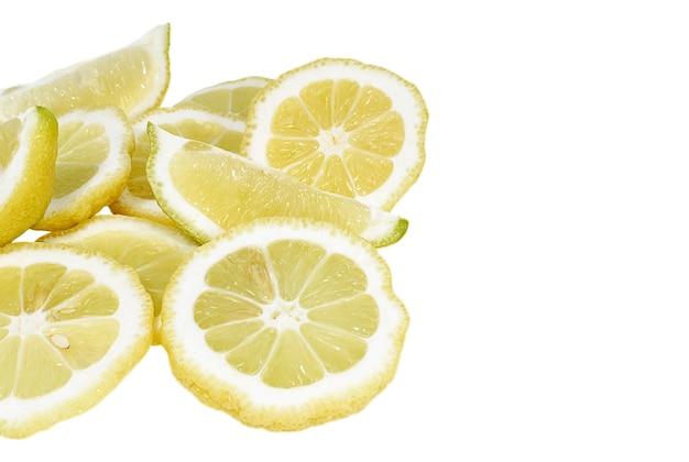 Куча свежих ломтиков лимона на белом фоне