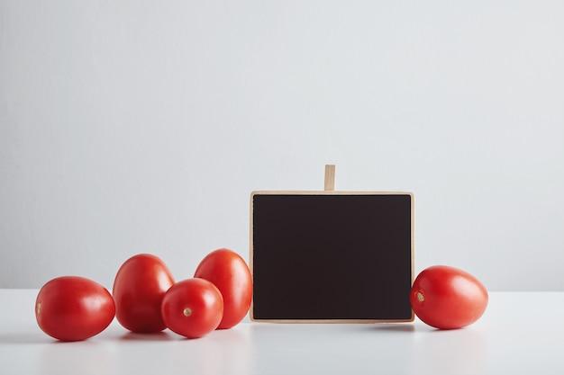 白いテーブルに分離されたチョークボードの値札が付いた新鮮な有機農場の赤いトマトのヒープ、販売の準備ができています。