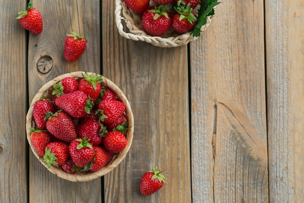 素朴な木製の背景のバスケットに新鮮なイチゴの山。健康的な食事とダイエット食品の概念。オーバーヘッド