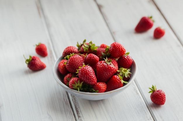 白い木製の背景の上のセラミックボウルに新鮮なイチゴの山。健康的な食事とダイエット食品の概念。