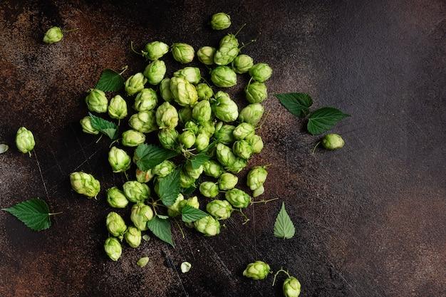Куча зеленого хмеля на темном гранж-фоне. крафтовое пиво и концепция пивоварения.