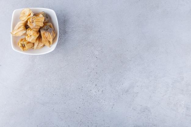건강 한 말린 된 cumquat 과일의 힙을 돌 테이블에 배치합니다.