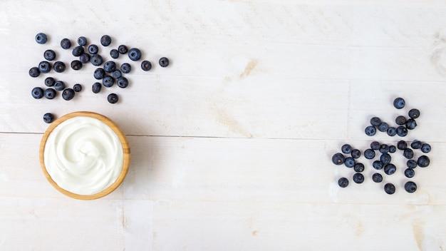Куча сочной черники и деревянная миска с гладким белым йогуртом на белом деревянном кухонном столе сверху
