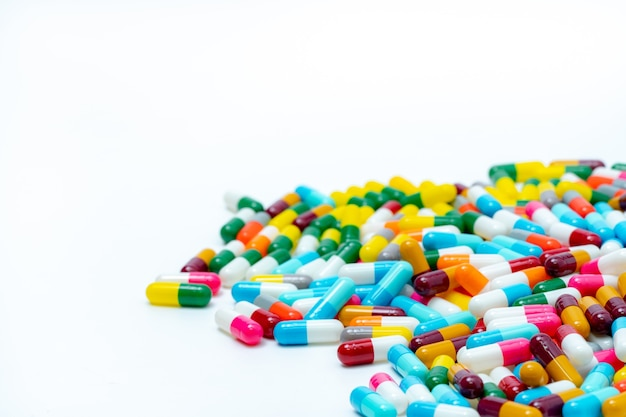 白い背景の上のマルチカラー抗生物質カプセルピルのヒープ。抗生物質。