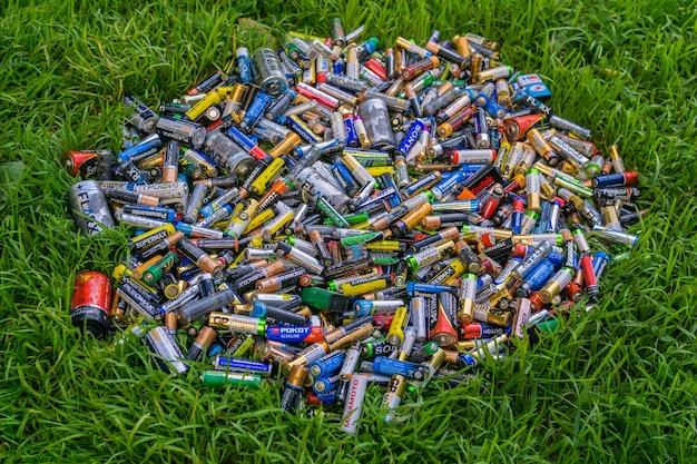 Куча старых использованных выброшенных элементов aa и других электрических батарей на траве