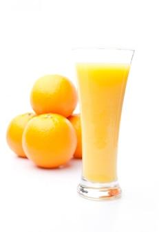 オレンジジュースのガラスの後ろにあるオレンジのヒープ
