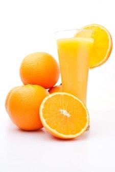 オレンジジュースのガラスの近くにオレンジのヒープ