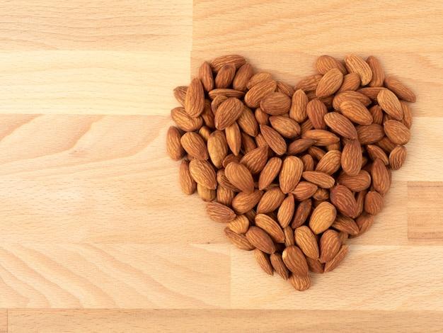 Куча органических миндальных орехов в форме сердца на деревянных