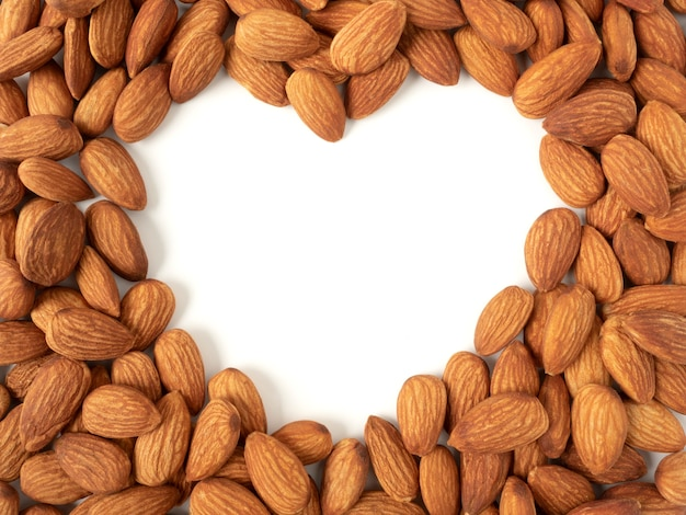 Куча органического миндаля в форме сердца сверху с белым пространством для копии миндальных орехов может улучшить сердце и здоровье.