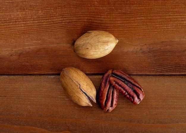 シェルのピーカンの山と木製のテーブルの装飾された皮をむいたナッツ。上面図