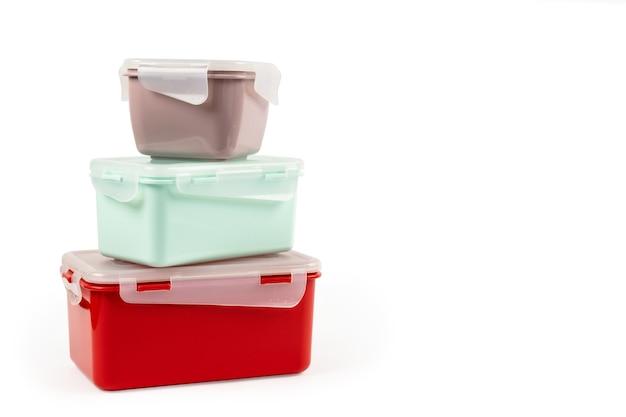 Куча пластиковых разноцветных контейнеров разных размеров для пищевых продуктов изолированы