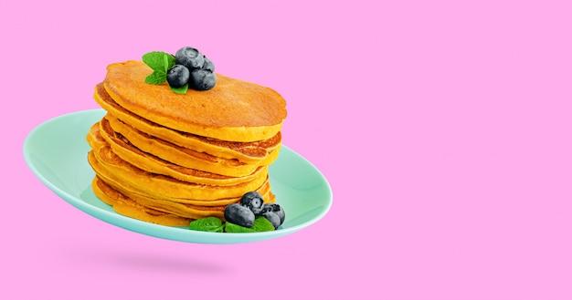 ブルーベリーとピンクの壁に分離されたターコイズブルーのプレートにミントとカボチャのパンケーキのヒープ。コピースペース