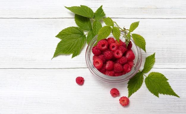 Куча малины лесная дикая малина. чаша с натуральными спелыми органическими ягодами с зелеными листьями на деревянном белом деревенском столе, вид сверху с копией пространства