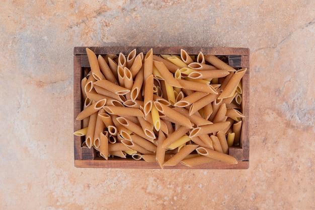 木製のバスケットに生の生パスタの山。高品質の写真