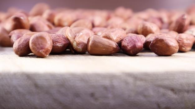 Куча сырого арахиса. арахис культурный, подземный или арахис. растение семейства бобовых. сельскохозяйственная культура в промышленных масштабах. родиной арахиса считается южная америка.