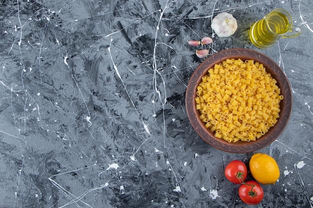 Куча сырых макаронных изделий с пипеткой в миске со свежими красными помидорами и маслом.