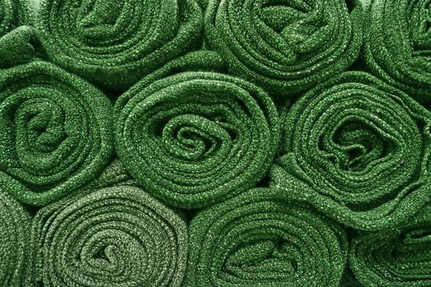 背景の重ねられたオリーブグリーンの毛布のヒープ